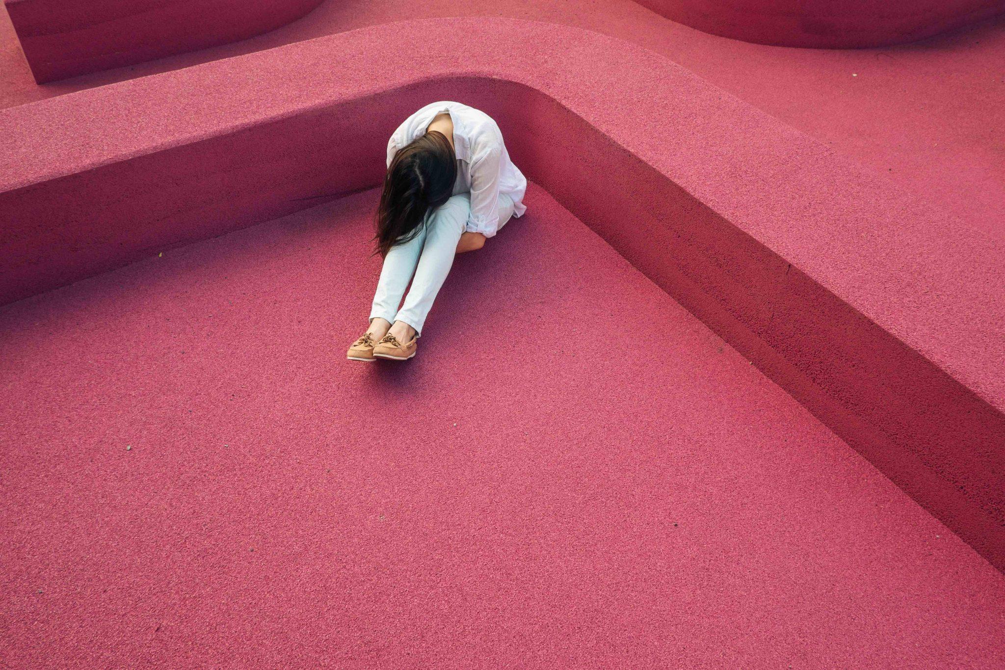 woman sitting red background, alcoholic hepatitis