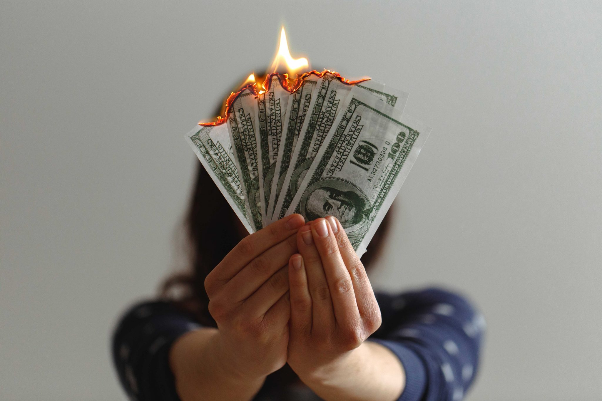 woman holding burning dollars how much do people spend on alcohol