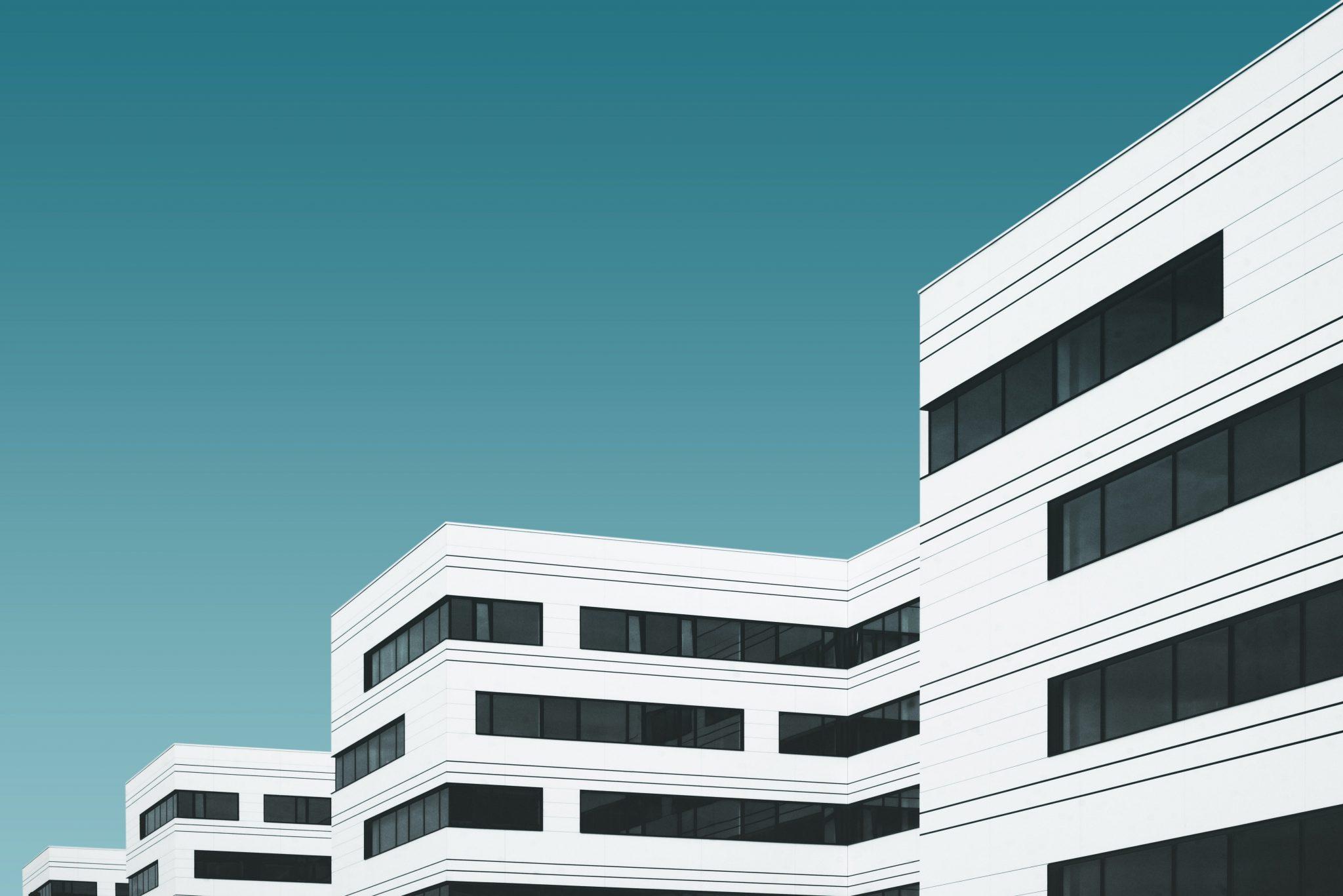 white buildings on blue background, rehab vs. online telehealth