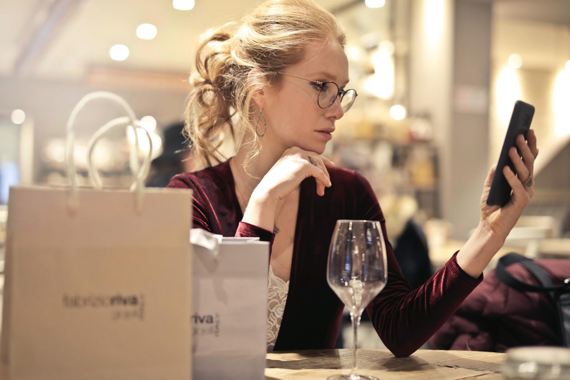 woman looking at phone with shopping bags