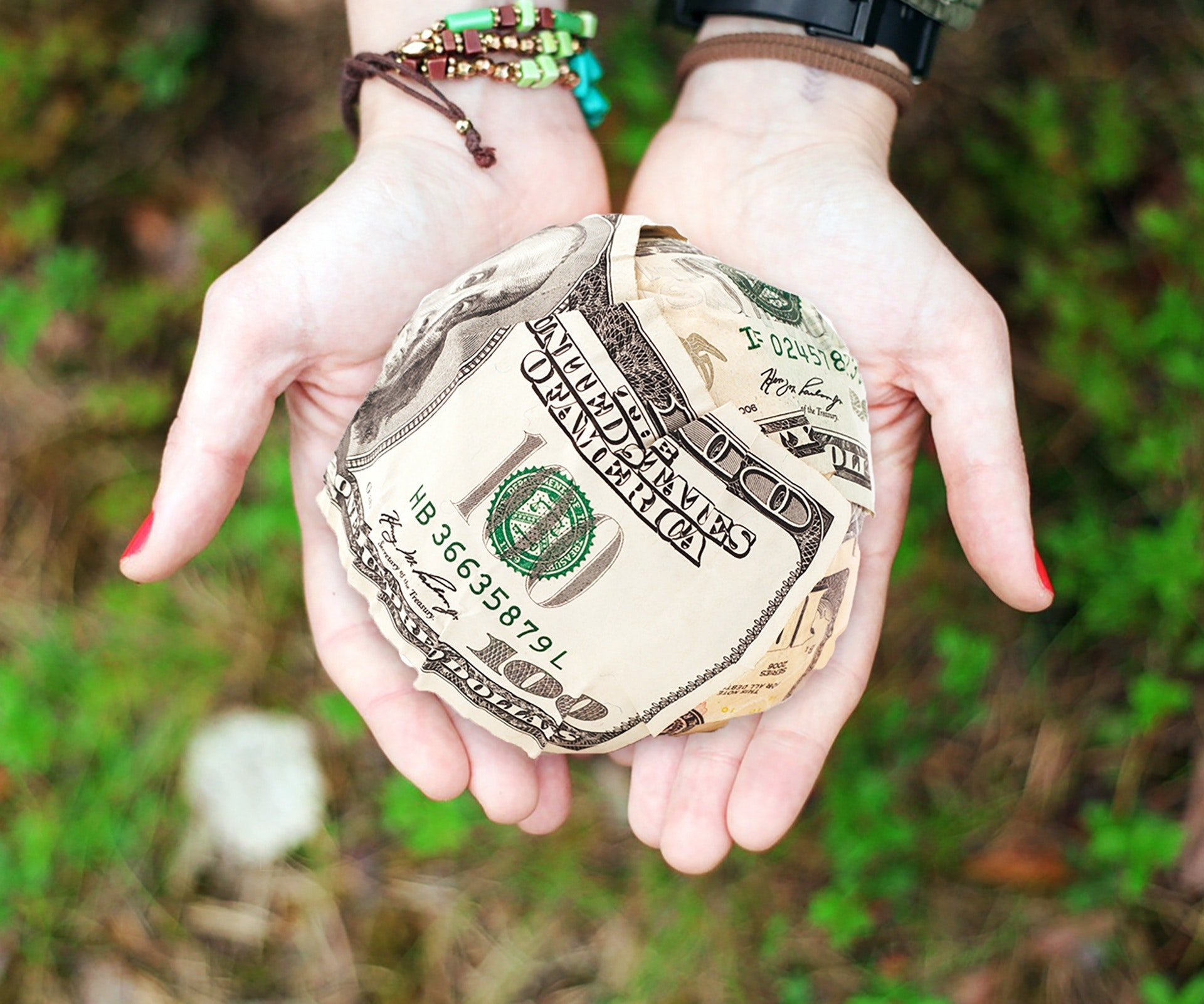 woman holding a ball made from dollars